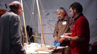 James and two others studying a boat model