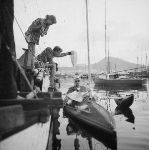 James greeting a man in a canoe approaching Tangaroa