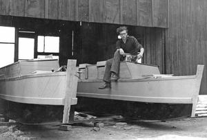 James Wharram sitting on one of the two completed hulls of Tangaroa