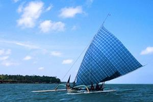 Double outrigger canoe with blue chequered sail