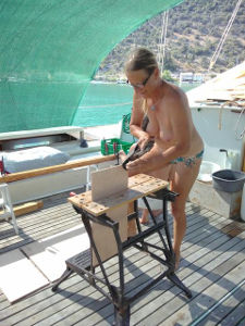 Hanneke using a planing tool on deck