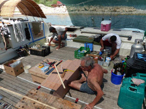 Generator being taken apart by Fabio, and shelves being built by Paul on Gaia's deck