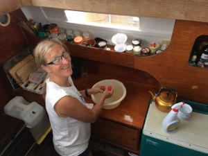 Hanneke in the galley with a wash bowl