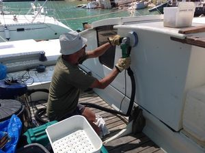 Paul kneeling down on deck, using a sander on a deckpod