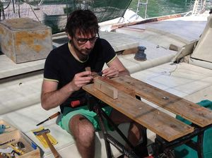 Giovanni with tools and workbench on deck