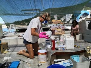 Hanneke mixing paint on deck and wearing a facemask. A crew member watches.