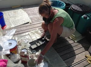 Amanda wearing facemask, with bucket of paint and roller tray