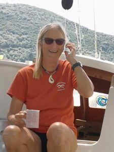 Hanneke on deck, smiling, holding a mug