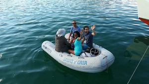 Four crew members in rubber dinghy, waving
