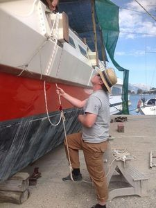 Bryce installing new beamlashings, using a rope loop which he is standing in to pull them tight