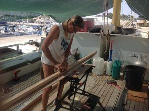 Hanneke sanding a piece of wood on deck