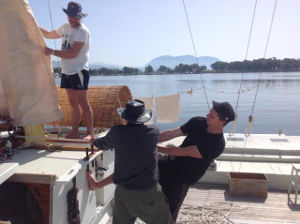 James with two helpers hoisting sails