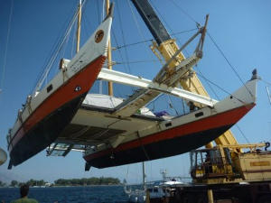 Large catamaran being lifted by crane