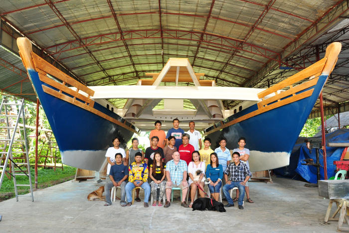 A team of boat builders with an almost-finished large blue catamaran under a shelter