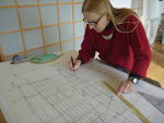 Hanneke Boon drawing boat building plans in the studio