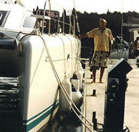 James Wharram standing next to a modern catamaran
