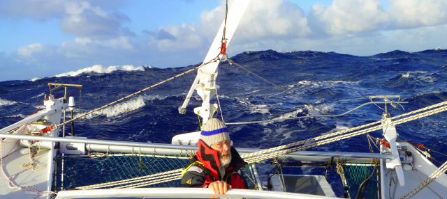 Don Brazier at the helm of Katipo in high seas