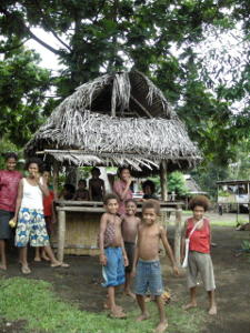 Villagers by a straw hut