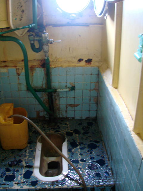 A shabby looking squat toilet