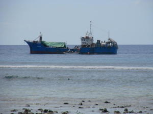 A blue cargo ship just off shore