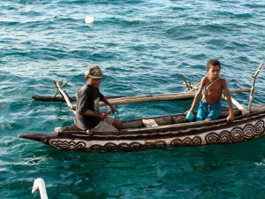 Local children in an outrigger canoe