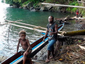 Locals with an outrigger canoe on the shore