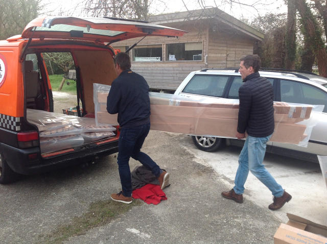 Men lifting plywood parts into a van