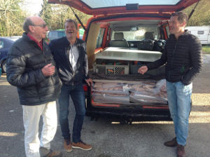 James with two men behind the van with tailgate open