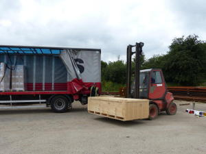 Shipping container being forklifted into a lorry