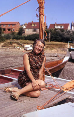Ruth Wharram on the deck of a beached catamaran