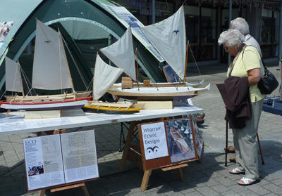 People studying boat models on a stand