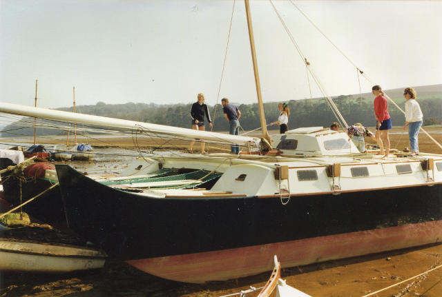 Pahi 42 on the beach with people aboard
