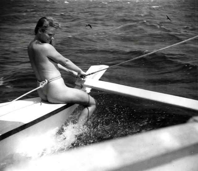 Jutta sitting on the port bow, feet splashing in the water
