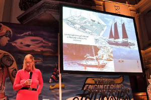 Hanneke Boon on stage, Wharram boats on a projector behind