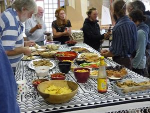 A table of food surrounded by party guests
