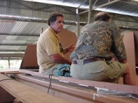 James sitting on an unfinished hull in workshop