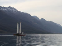 Catamaran sailing with mountains in the background