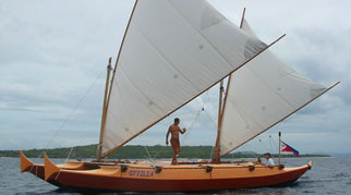 Tama Moana with sails up, people aboard