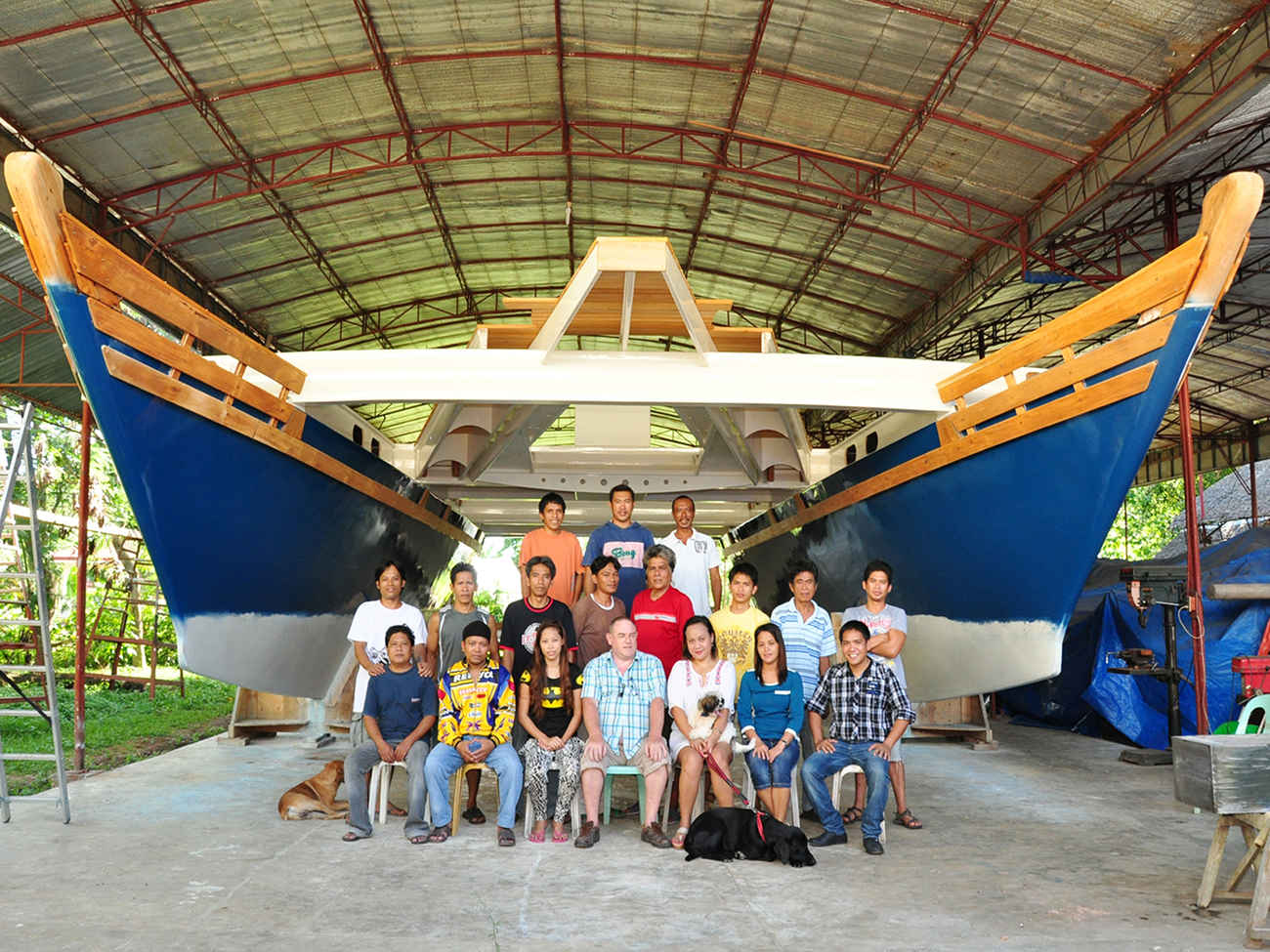 The Andy Smith Boatworks crew, posing for a photo under two large catamaran hulls
