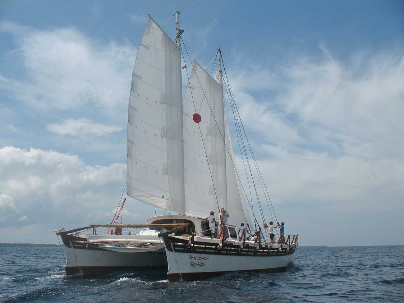 Rear view of Islander 65, wind in the sails, blue and cloudy sky