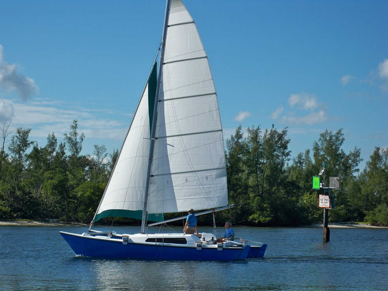 Blue Tiki 8m sailed by two people, trees in background