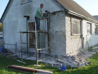 House with stripped walls and a man on scaffolding
