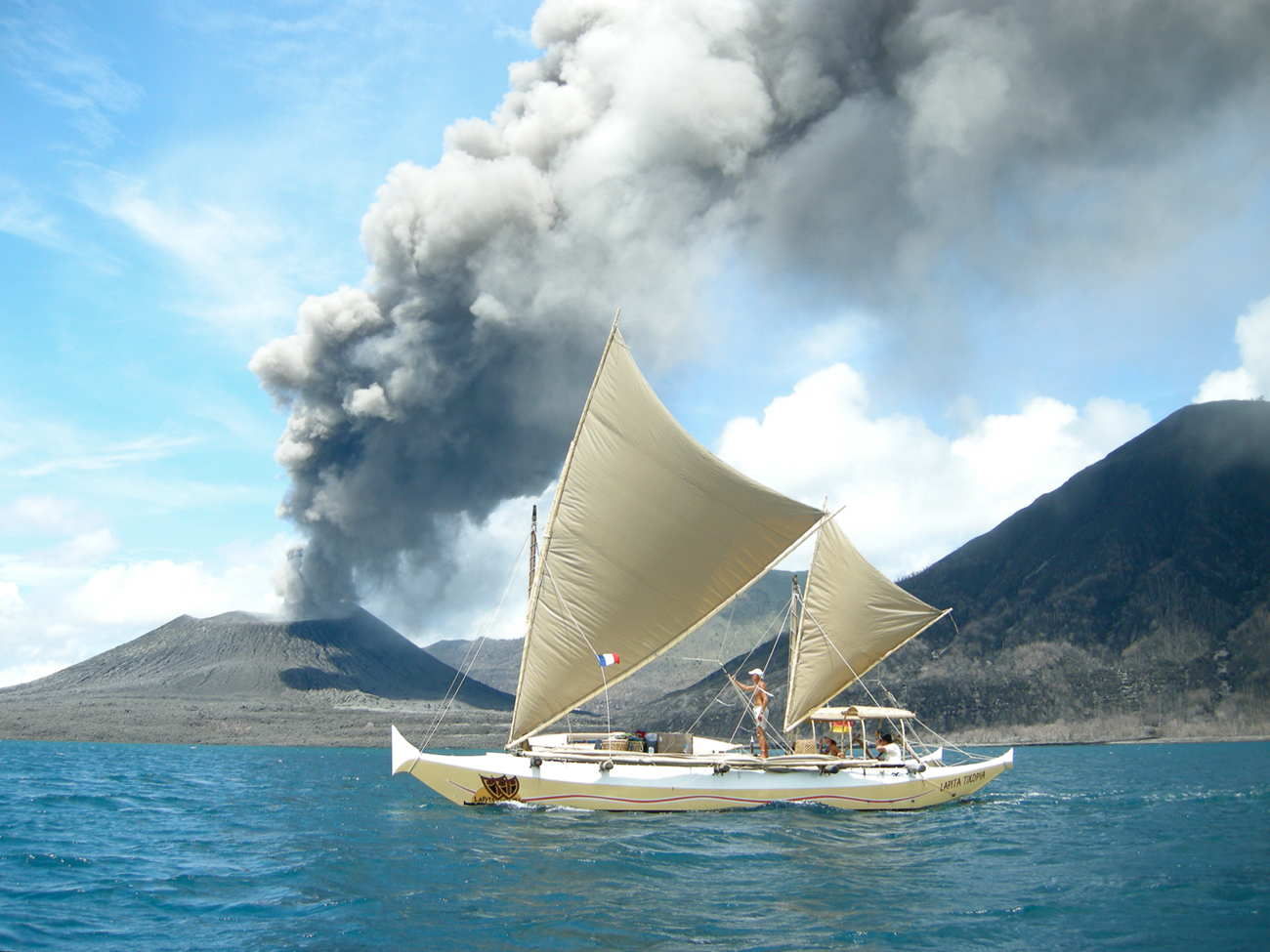Tama Moana sailing past a smoking volcano