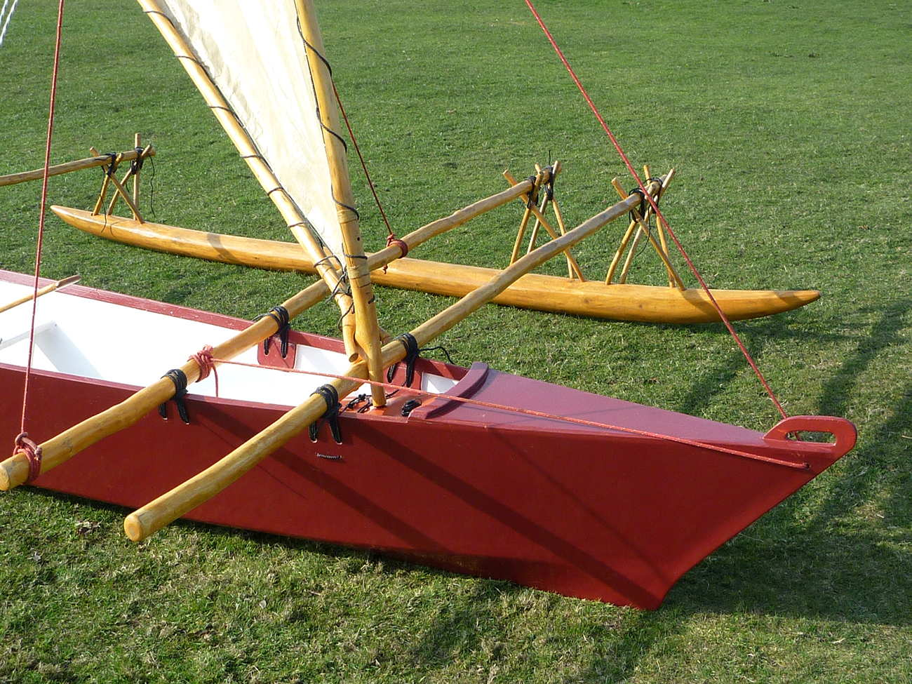 Dark red Melanesia outrigger canoe on land, close up of bow and float