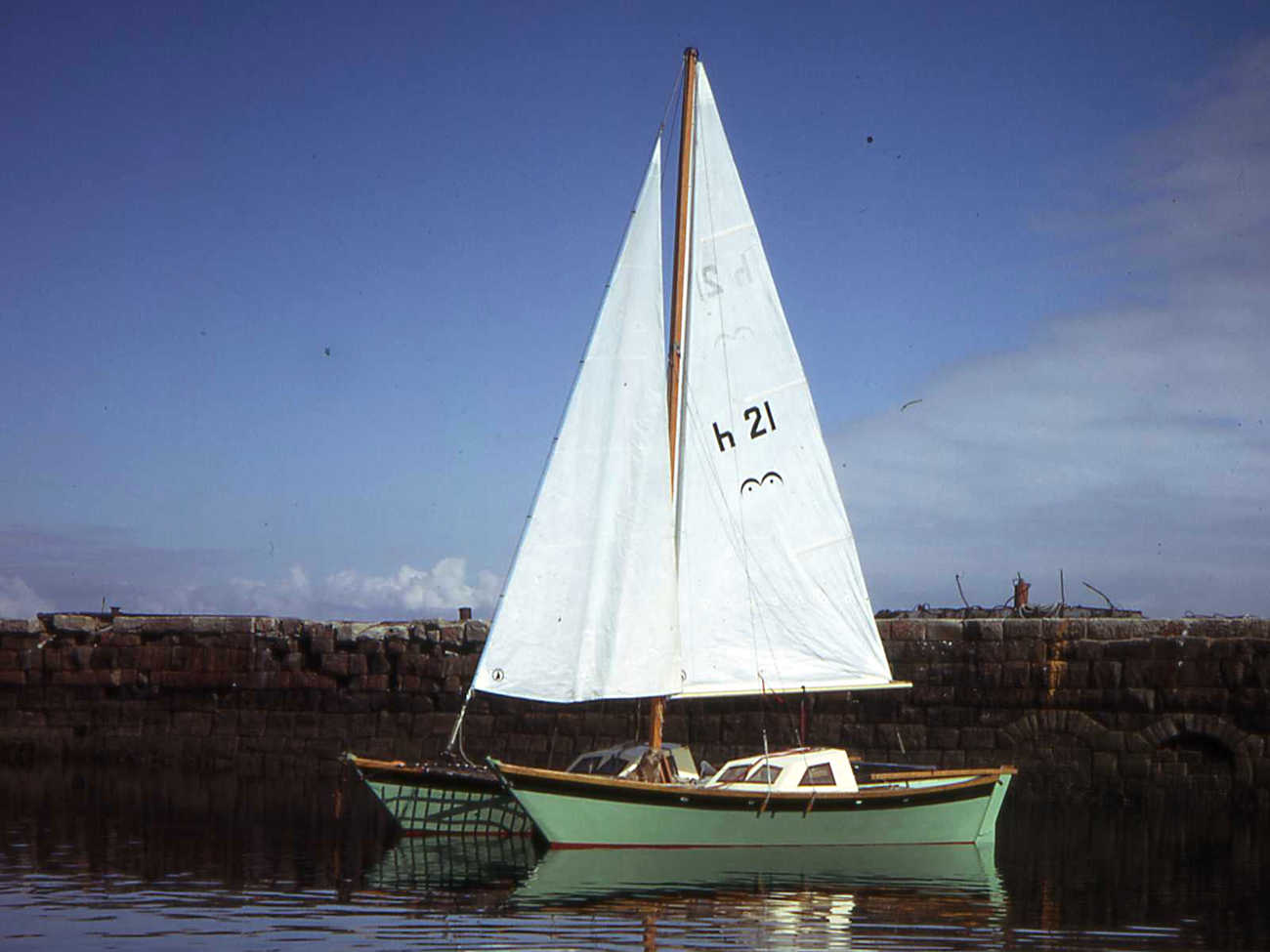 Hinemoa with green hulls and sails up, in a harbour