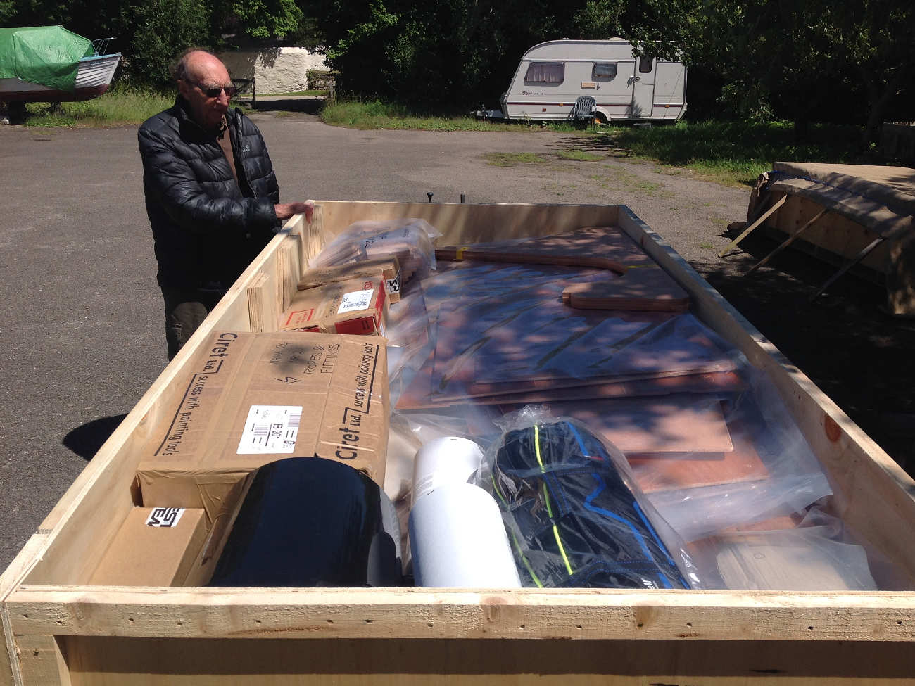A big box full of plywoood parts and other boat components