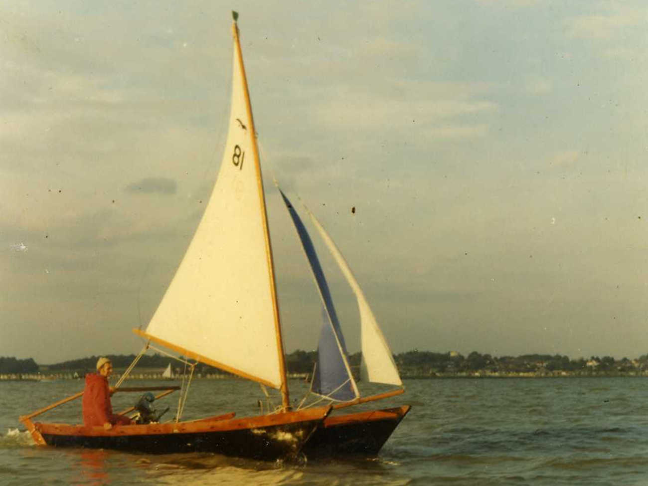 Maui with black hulls and white and blue sails, one man at the helm
