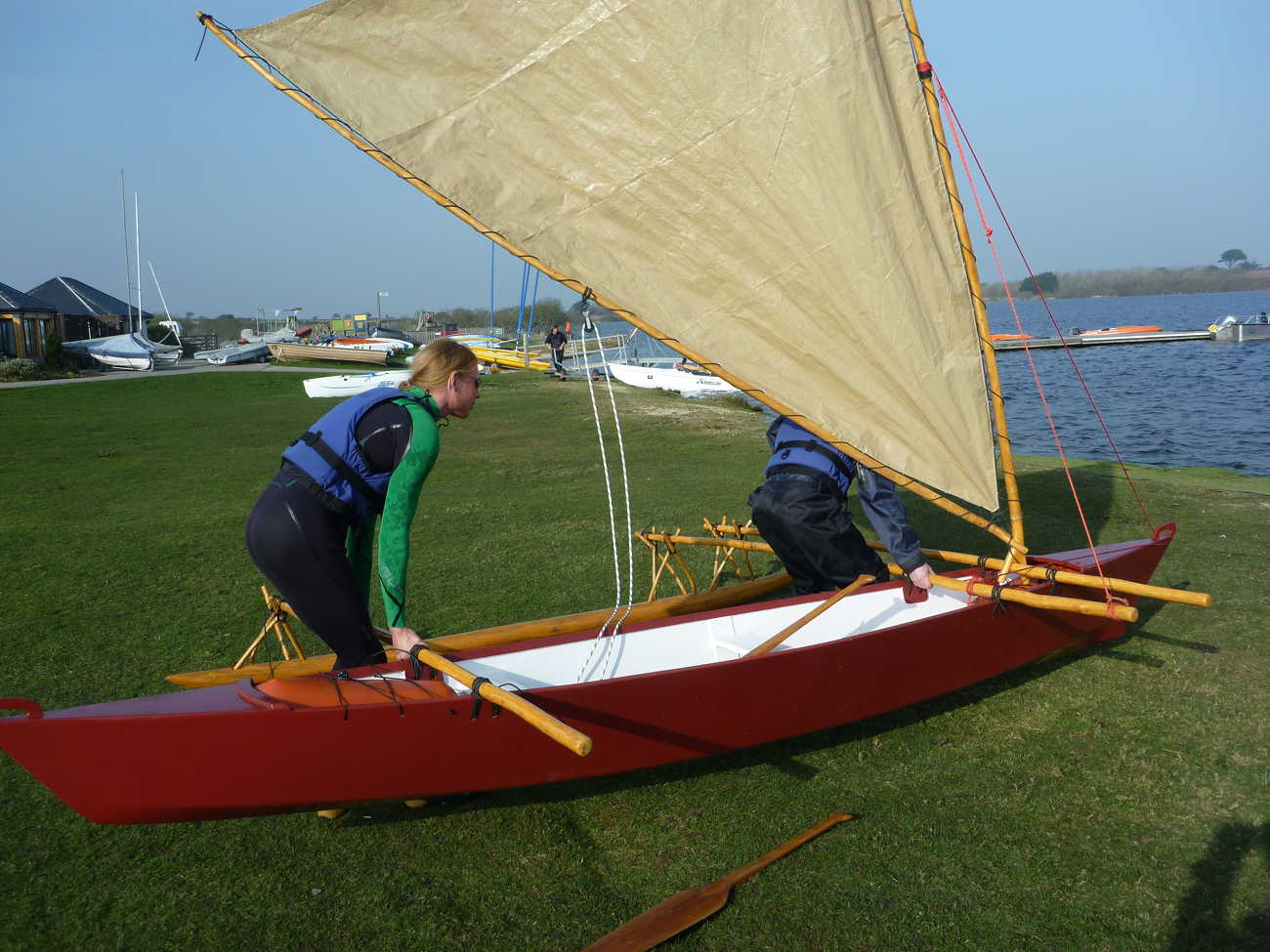 Red Melanesia outrigger canoe with crabclaw sail being carried by two towards the water