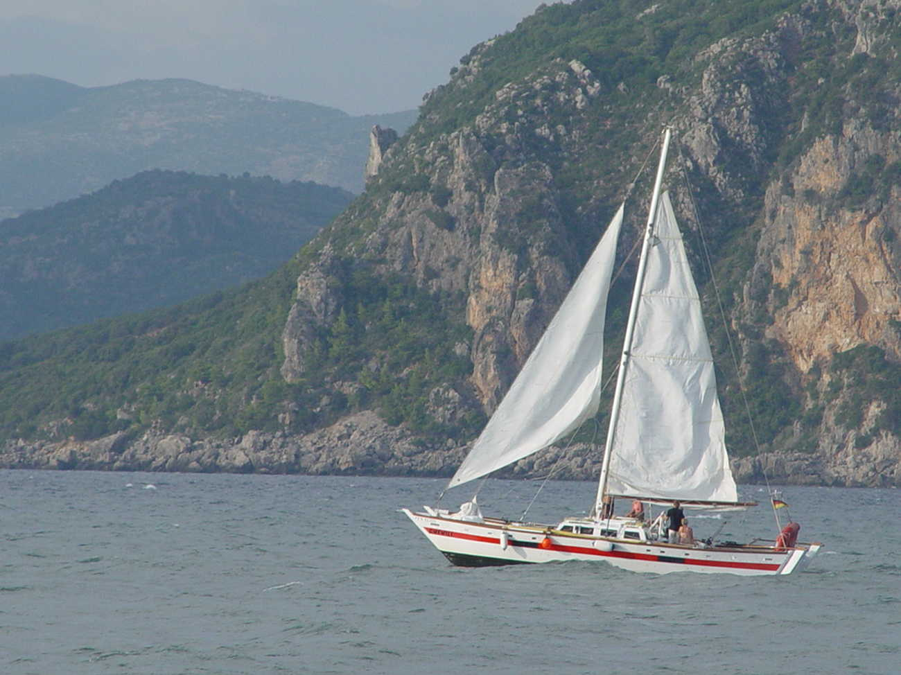 Red and white Narai, two people aboard, sailing against a backdrop of mountains covered in greenery