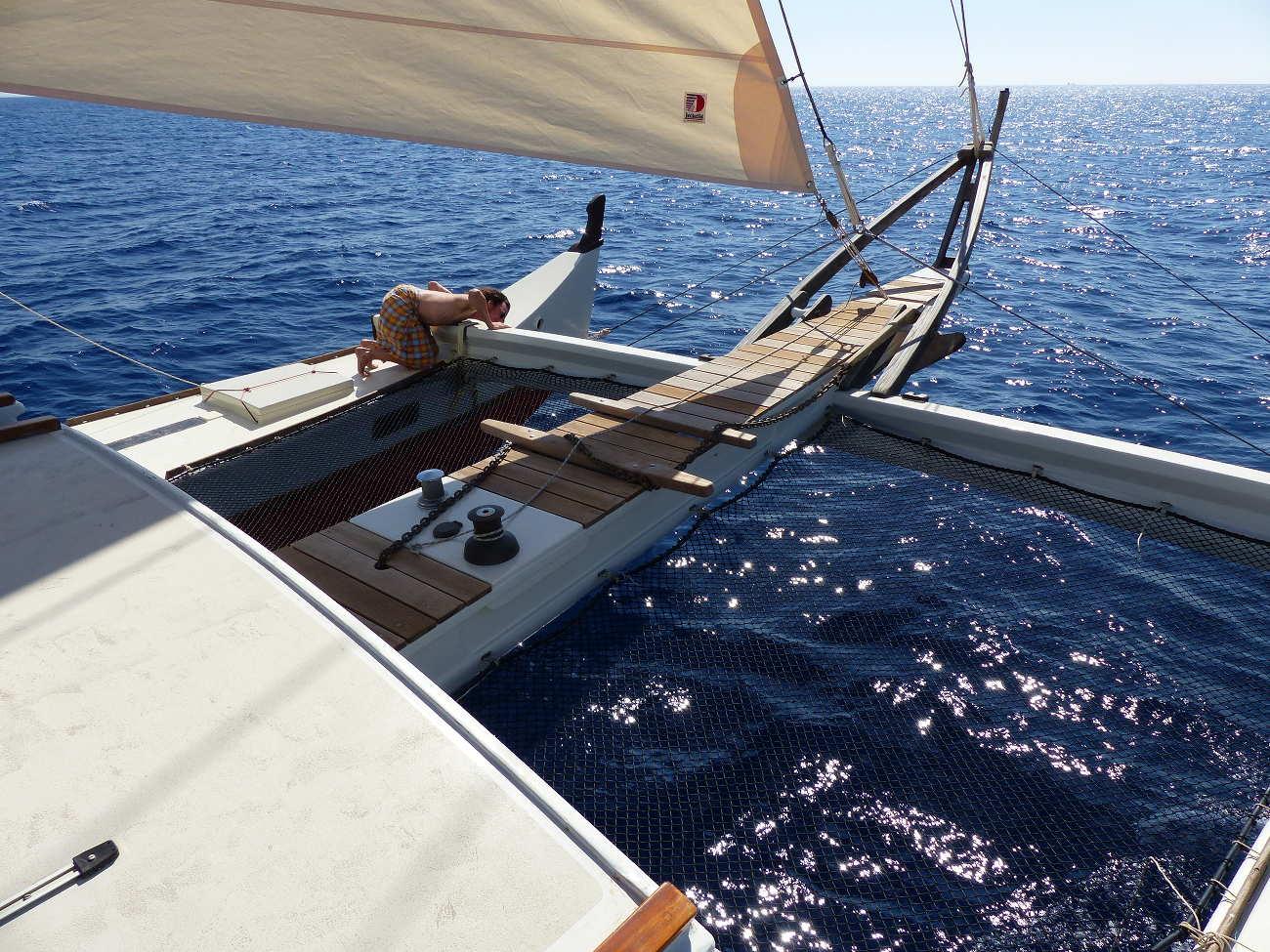 Pahi 63 bow trampoline, man leaning over and looking under hulls while boat is in motion